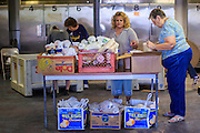07 AUGUST 2012 - TOLLESON, AZ: Volunteers set up a table at the food bank in Tolleson, AZ, about 15 miles west of Phoenix. The Tolleson food bank has been operating for more than 20 years. It used to serve mostly the families of migrant farm workers that worked the fields around Tolleson but in the early 2000's many of the farms were sold to real estate developers. Now the food bank serves both farm worker families and people who lost their homes in the real estate crash, that his Phoenix suburbs especially hard. More than 150 families a day are helped by the Tolleson food bank, an increase of more than 50% in the last five years.   PHOTO BY JACK KURTZ
