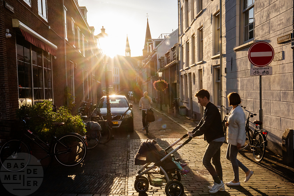 Een jong stel loopt met een kinderwagen door Utrecht, terwijl een man al bellend aan komt fietsen.<br /> <br /> A young couple walks with a stroller in Utrecht while a man calling is approaching on a bike.