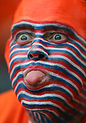 A Netherlands fan with his face painted sticks out his tongue