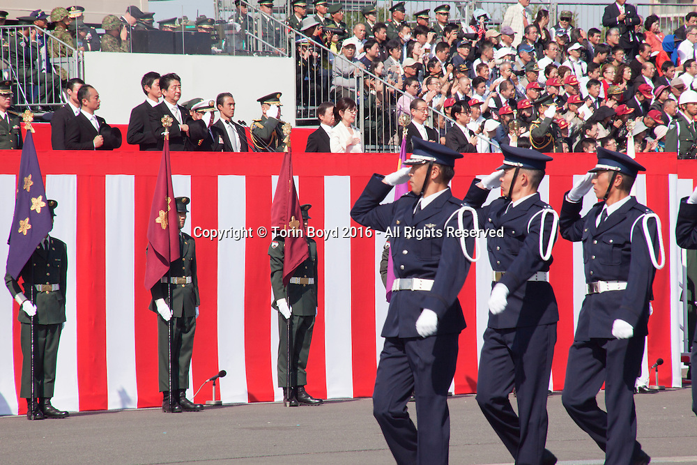 "October, 23, 2016, Asaka, Saitama Prefecture, Japan: Japanese Prime Minister Shinzo Abe proudly reviews his nation's military might during an annual review of the Japan Self Defense Force (JSDF), held at the Asaka Training Area on the outskirts of Tokyo. For this event, PM Abe, top ranking Japanese brass and international dignitaries were in attendance to view Japan's military prowess. This included 4000 troops, 27 divisions, 280 vehicles and artillery, plus 50 aircraft of the Ground, Air, and Maritime branches of the JSDF. Since the post WW II era, Japan has been a pacifist nation with it's constitution drafted by the Allied Occupation in 1947. But Since PM Shinzo Abe took office in 2012, he's had an agenda to revise the constitution which would permit Japan greater autonomy outside it's borders. In December 2013, Abe announced a five year plan of military expansion described as ""proactive pacifism"", with the goal of making Japan ""a more normal country"", able to defend itself. This was in reaction to China's buildup of it's military and territorial disputes with Japan, as well as a decreased American influence in the region. This is also a matter of national pride as Japan has been trying to wash away it's past aggressions of WW II. (Torin Boyd/Polaris)."