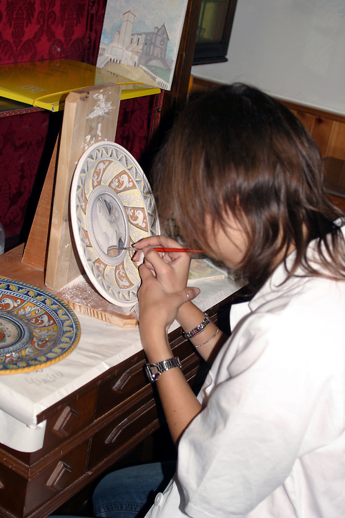 Deruta: An artist puts the final touches on a plate of typical Derutan design at Bottega dell'Artigiano.