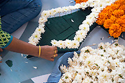 KOCHI, INDIA - 10th September 2019 - Women prepare a large scale pookalam motif for public display at a park in Kochi during Onam festival celebrations. Pookalam or Rangoli is one of the most popular traditional art forms in India. It is a kind of decorative motif, usually a floor art using various forms of colours from flowers and other colourful natural objects like spices and grains to create a decorative foral carpet. It is an integral part of Onam festival celebrations in Kerala. Kochi (Cochin), Kerala, Southern India.