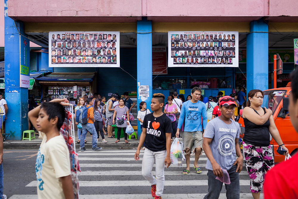 Davao City, Mindanao, Philippines - JUNE 18: Two large posters of Wanted Terrorist are seen posted at the busy crossing of Unitop Mall.  Security in the city is tight since President Duterte implemented a Martial Law for 60 days in Mindanao due to the heavy fighting in Malawi 250km away.