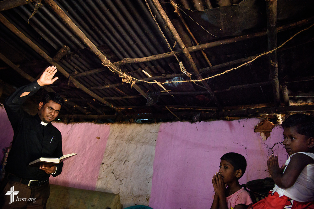 The Rev. P. Gnanakumar prays as he visits church members on the Eila rubber plantation in the Sabaragamuwa Province of Sri Lanka on Saturday, Jan. 20, 2018. The members praying with Gnanakumar are ostracized by the rest of their family for professing their faith in Christ. LCMS Communications/ Erik M. Lunsford