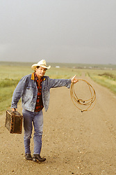 cowboy hitchhiking on a dirt road
