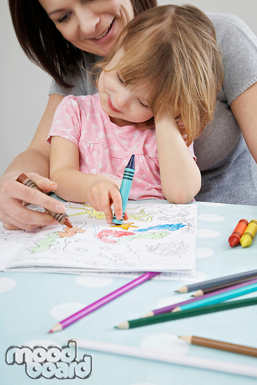 Mother helping daughter (3-4) with colouring in book