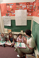 May 1998, Asheville, North Carolina, USA --- First grade students raise their hands during a reading circle in Mrs.Cathey's first grade class at Claxton Elementary School. Claxton is a public school in Asheville, North Carolina. --- Image by © Owen Franken