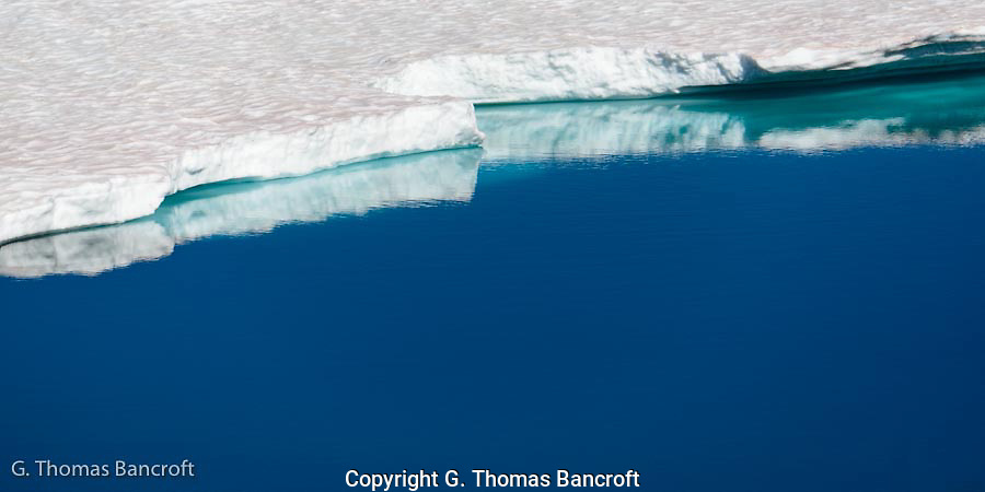 A snow bank extended down and across one side of Frozen Lake.  The edge of the bank was scalloped and reflected brilliantly in the blue water.  Riples across the snow added a nice contrast.