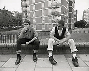 Two Teenagers Sitting In Urban Setting