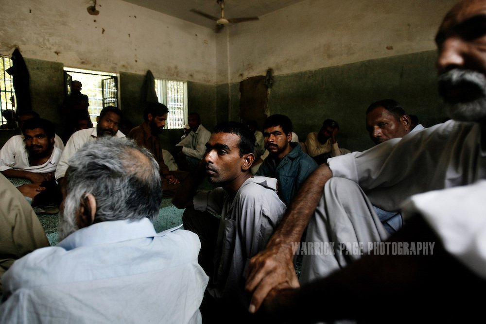 KARACHI, PAKISTAN - APRIL 18:  Mentally and physically handicapped men sit in a hallway of the Edhi Home for the disabled and homeless on April 18, 2008 in Karachi, Pakistan. Most of the men and children sit all day with noting to do and no way to occupy themselves and are rarely visited by family. The Edhi Foundation cares thousands of orphans, homeless, mentally and physically disabled Pakistanis throughout the impoverished nation. The Edhi Foundation represents a microcosm of Pakistan's dire poverty where children are often its first casualty, as tragedy and hope collide on a daily basis, and life and death are in constant flux existing only rooms apart. Pakistan is a country more than a third of it's population live in absolute poverty.  (Photo by Warrick Page)