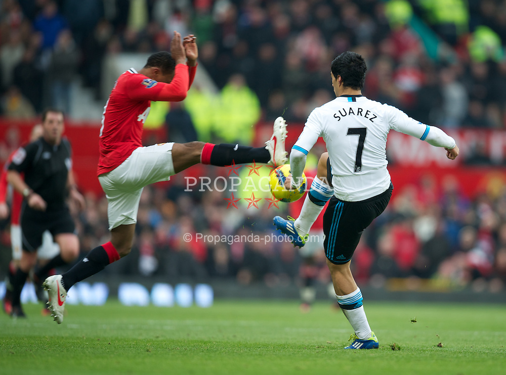 MANCHESTER, ENGLAND - Saturday, February 11, 2012: Manchester United's Patrice Evra dives in dangerously on Liverpool's Luis Alberto Suarez Diaz during the Premiership match at Old Trafford. (Pic by David Rawcliffe/Propaganda)