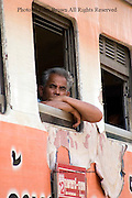 A man is looking out of a train window at the train station in Ubon Ratchathani, Thailand.