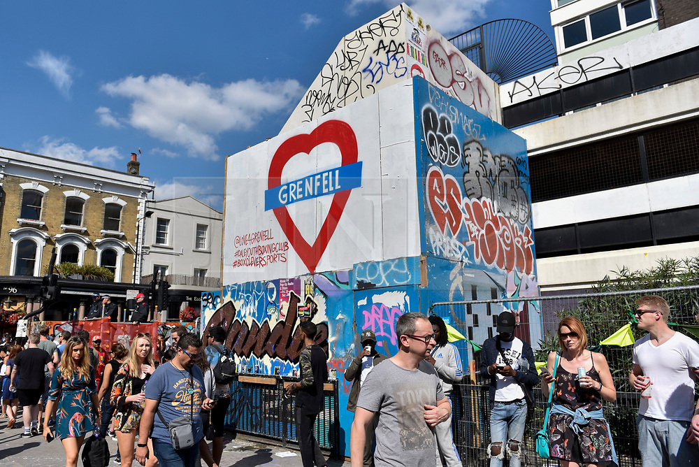 © Licensed to London News Pictures. 27/08/2017. London, UK. A street sign with a message of support for the victims of the Grenfell Tower fire is seen above members of the public enjoying during Family Day at the Notting Hill Carnival.  Over one million revellers are expected to attend Europe's biggest street party which takes place over the Bank Holiday Weekend. Photo credit : Stephen Chung/LNP