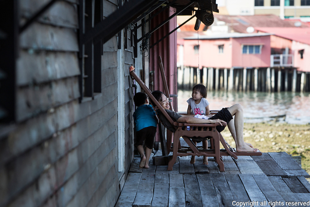 a father plays with his kids on a lazy sunday afternoon on the Chew Clan jetty, George Town,Penang, Malaysia
