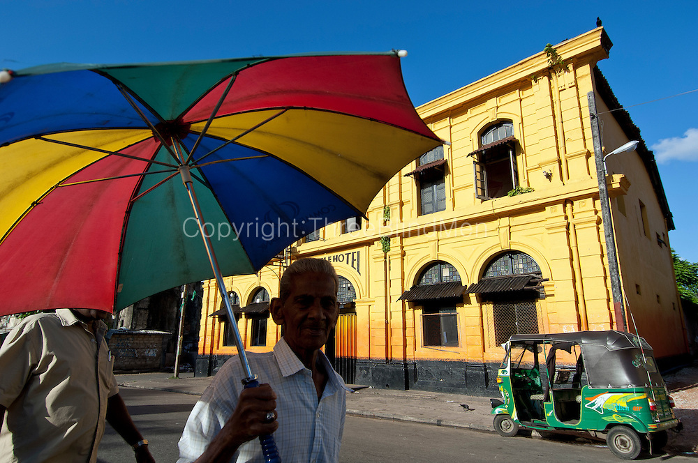 Hot afternoon - man and umbrella in front of the Castle Hotel in Slave Island, Colombo.