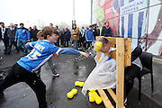 A young Brighton fan throws a soaking sponge at former player Guy Butters in the stocks for charity before the Sky Bet Championship match between Brighton and Hove Albion and Derby County at the American Express Community Stadium, Brighton and Hove, England on 2 May 2016.