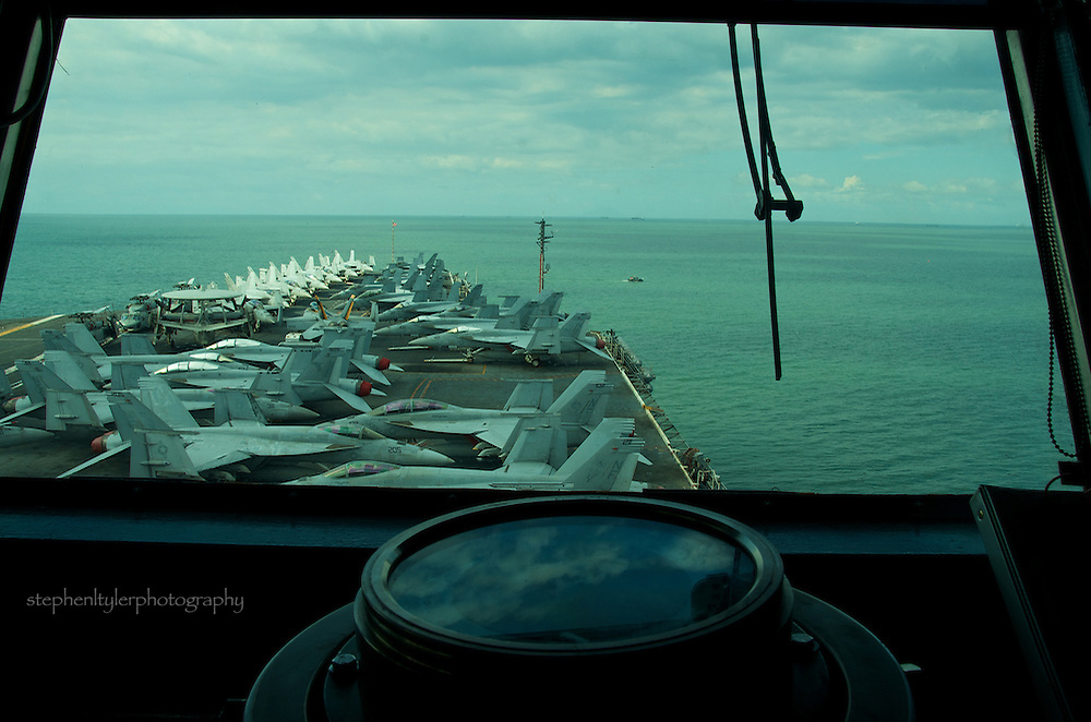 On the navigation deck (bridge) of the U.S.S. George Washington (CVN 73), Ensign Derrick Ingle explains a portion of the routine of driving the U.S. Navy's forward deployed aircraft carrier with the  capability of responding to  any crisis in the Asia Pacific region within 3 days.