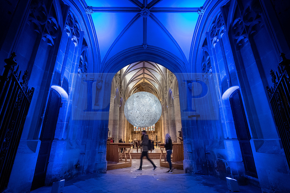 """© Licensed to London News Pictures 16/10/2019, Gloucester, UK. First day of """"The Museum of the Moon"""" a touring artwork by artist Luke Jerram, displaying a 3D replica of the Moon, internally lit and floating in the Nave of Gloucester Cathedral. The lunar imagery is accompanied by immersive surround sound composed by BAFTA award winner, Dan Jones.Photo Credit : Stephen Shepherd/LNP"""