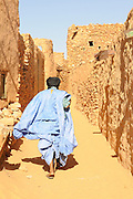 Man walking through the sandy lanes of the town of Chinguetti, Western Africa, Mauritania, Africa