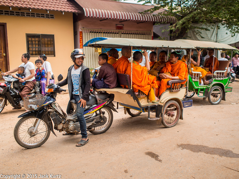15 MARCH 2015 - SIEM REAP, SIEM REAP, CAMBODIA: Buddhist monks in a tuk-tuk (three wheeled taxi) after the annual mass merit making at Wat Bo in Siem Reap. More than 1,200 Buddhist monks, from across Siem Reap province, received alms from Buddhist lay people during the morning long ceremony. Wat Bo was originally built to be a the temple for Siamese (Thai) troops when Siem Reap and western Cambodia were controlled by Siam (Thailand). Now Wat Bo is one of the most important temples in Siem Reap.      PHOTO BY JACK KURTZ