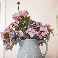 Pink and purple garden flowers in a bluse decorative vase in an interior setting
