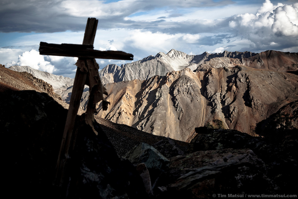 A silhouetted cross overlooks the rocky mountains in Colorado near the Maroon Bells.