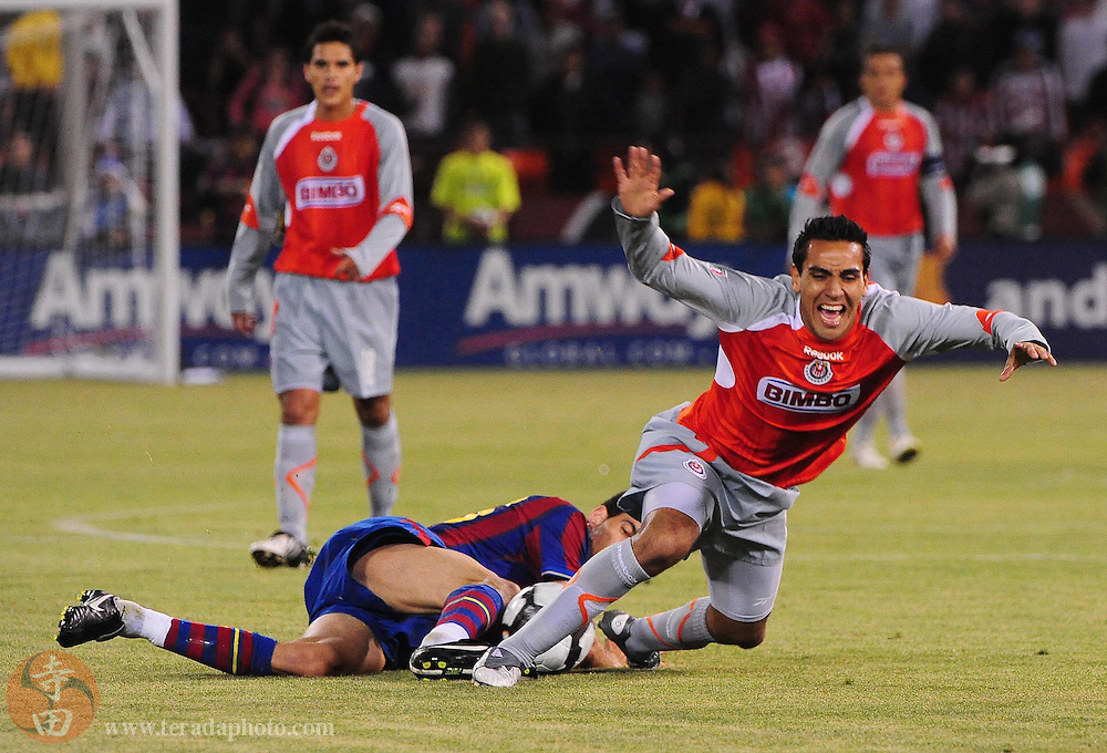August 8, 2009; San Francisco, CA, USA; Chivas de Guadalajara forward Jesus Padilla (right) is tripped by FC Barcelona midfielder Sergi Busquets (left) during the second half in the Night of Champions international friendly contest at Candlestick Park. The game ended in a 1-1 tie.