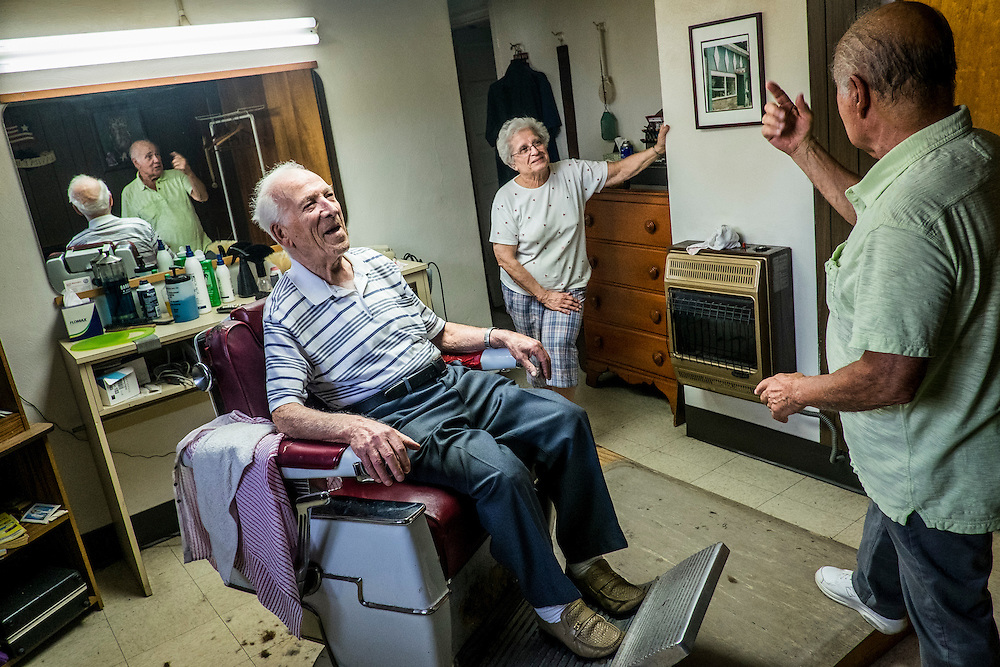 As his wife Margie looks on, John Talarico (center)  talks  politics with Monessen Mayor Lou Mavrakis in Tallarico&rsquo;s barber shop in the basement of his home in Monessen. Pa.<br />