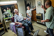 As his wife Margie looks on, John Talarico (center)  talks  politics with Monessen Mayor Lou Mavrakis in Tallarico's barber shop in the basement of his home in Monessen. Pa.<br /> <br /> Monessen, a third-class city, faces the same problems as th other former steel towns — declining population and tax revenue after the mills shut down. The city's population has dropped to 7,600 from a high of 20,268 in 1930.