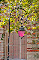 Pretty pink spiral iron lamp in the historic city of Arles, France.