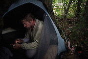 "DACULA, GA – JUNE 6, 2014: Karl Bushby rests in a tent after walking several miles on Highway 124 in Georgia. ""If I'm not walking, I'm either waiting to get walking or planning for the next part of the journey."" <br /> <br /> Karl Bushby is trying to complete the longest walk in history. Unless the Russians stop him. As a 45 year-old Brit, Bushby been traveling around the world on foot since 1998. In the most recent leg of his journey, Bushby is walking to Washington, D.C. to petition the Russian Embassy to lift a visa ban that prohibited him from continuing his hike through Russia."