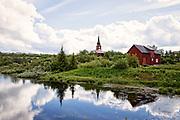 Kautokeino kirke, Guovdageainnu. Kautokeino kirke er en kirke konstruert i en rektangulær form (langkirke), fra 1958 i Kautokeino kommune, Finnmark fylke. Kirkebygget ligger på østsiden av Kautokeinoelven, sør for Kautokeino sentrum.<br /> Alteret og altertavlen.<br /> Byggverket er i tre og har 300 plasser. Altertavlen er malt av Jørgen Mudd og framstiller Jesus som en hyrde. Lysekronene fra kirken som ble brent i 1944 er bevart og henger i kirken. <br /> Bygget av Sverige i 1701, brent av tyske styrker i 1944, gjenreist 1958. (W) Kautokeino kirke ble bygget i 1958 på tomten etter Kautokeino gamle kirke, som ble brent av tyskerne i 1944. Nest etter det ortodokse kapellet i Neiden, som er fra 1500-tallet, var dette den eldste kirkebygningen i Finnmark, bygget rundt 1701. Den nye kirken, som er en langkirke av tre, er tegnet av arkitekt Finn Bryn. <br /> Innvendig i kirkerommet er veggene kledd med malt møllerstuepanel og gulvet skiferlagt. Orgelgalleriet er bygget over våpenhuset. Korpartiet, som er løftet to trappetrinn opp fra gulvnivået i kirkerommet, går ellers i flukt med kirkerommets vegger og tak. Korets grunnplan er halvt åttekantet, slik at rommet smalner og avrundes mot veggen bak alteret. Den tredelte himlingen over kirkerom og korparti løfter seg fra et smalt flatt felt som løper sammenhengende langs veggene. <br /> Altertavlen er malt av Jørg Mind i 1958 og forestiller Jesus som den gode hyrde. I gavlfeltet er det et forgylt treenighetssymbol. Alterbildet er flankert av utskrånende, rettsidete vingefelt, en form som også gjentas på benkevangene i kirkerommet. Alterfronten er dekorert med Kristusmonogrammet og tegnene for alfa og omega, begynnelsen og slutten. Messinglysekronene er fra den gamle kirken og ble reddet fra brannen i 1944. <br /> Kilder: NIKUs kirkeregister<br /> Rasmussen, Alf Henry: Våre kirker. Norsk kirkeleksikon, Kirkenær 1993<br /> Steen, Adolf: Kautokeino gamle kirke, i ARA serien, Sami varas, Trondheim 1969.