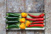 Close up of red, green and yellow hot peppers arranged on rectangular tray on old  wooden table