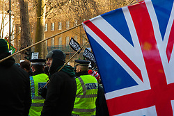 London, February 8th 2015. Muslims demonstrate outside Downing Street  to denounce the uncivilised expressionists reprinting of the cartoon image of the Holy Prophet Muhammad. PICTURED: A small group of anti-Islamist counter protesters from Britain First stand firm as thousands of Mulims demonstrate across the road on Whitehall.