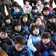 OGA, JAPAN - MARCH 17: Students at the Hokuyou Elementary School listens to instructions of the officials during a missile evacuation drill on Friday, March 17, 2017, in Kitaura, Oga, Akita Prefecture, Japan. During the drill, around 50 kids were instructed to walk slowly inside of a school gym, as if a missile had hit the the ground nearby. After a loud siren, people are instructed through a loudspeaker to move to safer ground in the school. People participated in the first missile evacuation drill organized by the Akita prefectural office and Oga city to prepare people in the event of a North Korean Missile strike on Japan. Recently, Three of four missiles fired by North Korea may have fallen into Japan's Exclusive Economic Zone and the Japanese government has lodged a strong protest against North Korea. (Photo: Richard Atrero de Guzman/ANADOLU Agency)
