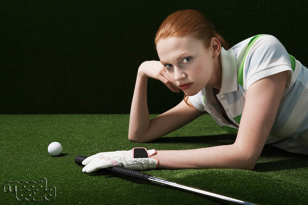 Woman reclining on floor with golf club and ball portrait