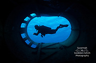 Grand Cayman - A diver is cast in silhouette in the smokestack of the Kittiwake shipwreck.