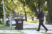 13 September 2010: A Springfield Police officer protects himself with a shield as he walks into the line of fire early in a four and a half hour stand off between police and a barricaded subject Monday afternoon. The subject took hold in a house on West State Street in Springfield. Credit: David Welker/ Turfimages.com