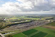Nederland, Zuid-Holland, Zwijndrecht, 23-10-2013; Kijfhoek, rangeerterrein voor goederentreinen. Overzicht van de verdeelsporen. Kijfhoek huisvest Keyrail, exploitant Betuweroute en is in beheer bij ProRail. De Betuweroute, die begint als Havenspoorlijn op de Maasvlakte, verbindt via Kijfhoek de Rotterdamse haven met het achterland. Het rangeeremplacement dient voor het sorteren van goederenwagons waarbij gebruik gemaakt wordt van de zwaartekracht, het 'heuvelen': de wagons worden de heuvel opgeduwd, bij het de heuvel afrollen komen ze, door middel van wissels, op verschillende verdeelsporen. Railremmen zorgen voor het automatisch remmen van de wagons. Na het heuvelproces staan de nieuw samengestelde treinen op aparte opstelsporen.<br /> Kijfhoek, railway yard used by ProRail and Keyrail (Betuweroute operator). Kijfhoek connects via the Betuweroute (beginning as Havenspoorlijn on the Maasvlakte), through the port of Rotterdam with the hinterland. The shunting yard for sorting wagons makes use of gravity. The new trains are assembled on separate tracks.<br /> luchtfoto (toeslag op standard tarieven);<br /> aerial photo (additional fee required);<br /> copyright foto/photo Siebe Swart