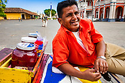 "09 JANUARY 2007 - GRANADA, NICARAGUA: A ""raspado"" vendor rests on his cart on the plaza in Granada, Nicaragua. Raspados are water and fruit juice served on shaved ice. Granada, founded in 1524, is one of the oldest cities in the Americas. Granada was relatively untouched by either the Nicaraguan revolution or the Contra War, so its colonial architecture survived relatively unscathed. It has emerged as the heart of Nicaragua's tourism revival.  Photo by Jack Kurtz / ZUMA Press"