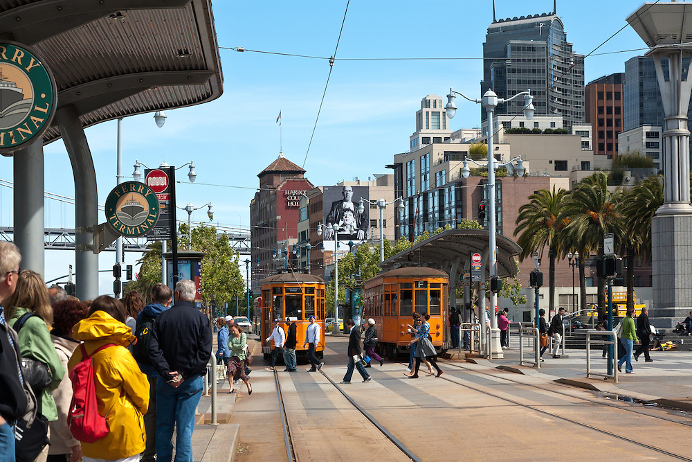 """San Francisco, CA:  Two Peter Witt vintage trolleys from Milan roll down the F-Line that loops and links Market Street, the Ferry Building, and Fishermen's Wharf.  <br /> <br /> From the Market Street Railway website: """"In addition to its world-famous cable car fleet, the San Francisco Municipal Railway (Muni) owns some ninety historic streetcars, trolleys, and trams (names used in different parts of the world to describe electric rail vehicles capable of running on city streets). About half of these streetcars are in active service, or being prepared for it; the remainder are currently non-operational, unrestored cars that could be used for future service expansion.<br /> <br /> Three general types of vintage streetcars are used in San Francisco: a collection of unique vintage cars from both San Francisco and around the world; streamlined art deco PCC streetcars from the 1940s and 1950s that provide the backbone of daily service; and 1920s Peter Witt trams from Milan, Italy, which also operate daily. <br /> <br /> This older type of streetcar was designed by Cleveland transit leader Peter Witt and ran in many US cities, though never in San Francisco. Milan, Italy built hundreds of Peter Witts in 1928 and are still running some today. Muni got one car, No. 1834, as a Trolley Festival gift in 1984 and liked it so much they obtained ten more in 1998 to meet the huge F-line rider demand.<br /> <br /> The Peter Witts entered Muni service still wearing the solid orange livery used in Milan for the past quarter-century. In 2004, however, car No. 1811 was repainted into the original 1928 Milan livery of yellow and white with black trim. In 2007, No. 1818 received the two-tone green livery that the Milan trams wore from the 1930s to the 1970s. Market Street Railway has suggested to Muni that as these cars are repainted, the fleet is balanced between the three historic Milan liveries (yellow, green, and orange). <br /> <br /> Some of the Milan trams retain their original Mila"""