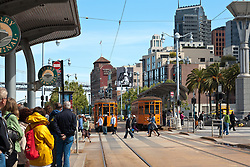 San Francisco, CA:  Two Peter Witt vintage trolleys from Milan roll down the F-Line that loops and links Market Street, the Ferry Building, and Fishermen's Wharf.  <br /> <br /> From the Market Street Railway website: &quot;In addition to its world-famous cable car fleet, the San Francisco Municipal Railway (Muni) owns some ninety historic streetcars, trolleys, and trams (names used in different parts of the world to describe electric rail vehicles capable of running on city streets). About half of these streetcars are in active service, or being prepared for it; the remainder are currently non-operational, unrestored cars that could be used for future service expansion.<br /> <br /> Three general types of vintage streetcars are used in San Francisco: a collection of unique vintage cars from both San Francisco and around the world; streamlined art deco PCC streetcars from the 1940s and 1950s that provide the backbone of daily service; and 1920s Peter Witt trams from Milan, Italy, which also operate daily. <br /> <br /> This older type of streetcar was designed by Cleveland transit leader Peter Witt and ran in many US cities, though never in San Francisco. Milan, Italy built hundreds of Peter Witts in 1928 and are still running some today. Muni got one car, No. 1834, as a Trolley Festival gift in 1984 and liked it so much they obtained ten more in 1998 to meet the huge F-line rider demand.<br /> <br /> The Peter Witts entered Muni service still wearing the solid orange livery used in Milan for the past quarter-century. In 2004, however, car No. 1811 was repainted into the original 1928 Milan livery of yellow and white with black trim. In 2007, No. 1818 received the two-tone green livery that the Milan trams wore from the 1930s to the 1970s. Market Street Railway has suggested to Muni that as these cars are repainted, the fleet is balanced between the three historic Milan liveries (yellow, green, and orange). <br /> <br /> Some of the Milan trams retain their original