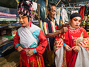"18 AUGUST 2014 - BANGKOK, THAILAND:       Members of the Lehigh Leng Kaitoung Opera troupe get ready to go on stage before a performance at Chaomae Thapthim Shrine, a small Chinese shrine in a working class neighborhood of Bangkok. The performance was for Ghost Month. Chinese opera was once very popular in Thailand, where it is called ""Ngiew."" It is usually performed in the Teochew language. Millions of Chinese emigrated to Thailand (then Siam) in the 18th and 19th centuries and brought their culture with them. Recently the popularity of ngiew has faded as people turn to performances of opera on DVD or movies. There are still as many 30 Chinese opera troupes left in Bangkok and its environs. They are especially busy during Chinese New Year and Chinese holiday when they travel from Chinese temple to Chinese temple performing on stages they put up in streets near the temple, sometimes sleeping on hammocks they sling under their stage. Most of the Chinese operas from Bangkok travel to Malaysia for Ghost Month, leaving just a few to perform in Bangkok.   PHOTO BY JACK KURTZ"