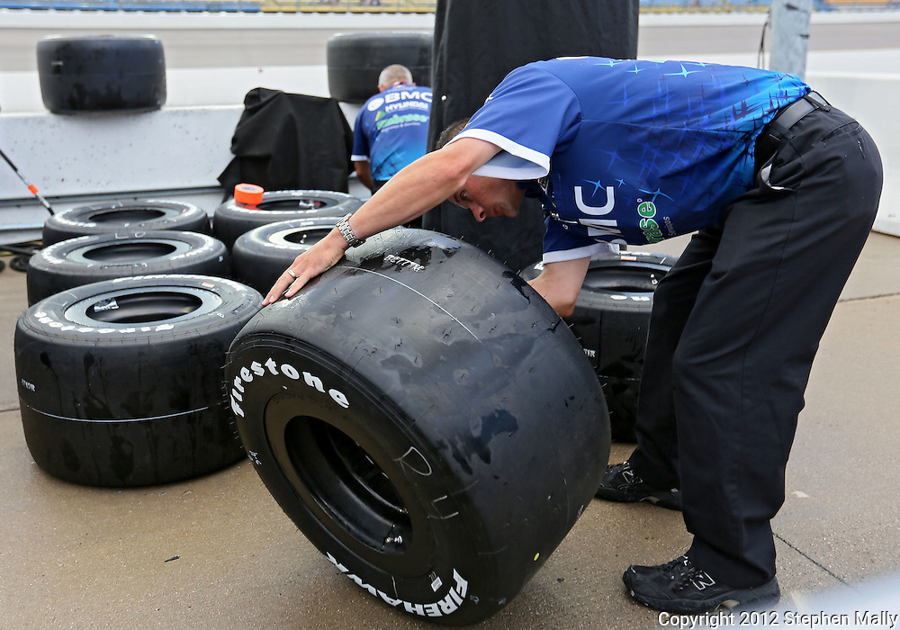 A worker wipes down the tires in the pit of Rubens Barrichello before the start of the IZOD IndyCar Iowa Corn Indy 250 auto race at the Iowa Speedway in Newton, Iowa on Saturday, June 23, 2012.