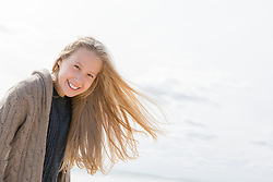 portrait of a little blonde girl at the beach during the Fall season