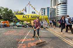 © Licensed to London News Pictures. 17/07/2019. Leeds, UK. An activist sweeps the road this morning as the Extinction Rebellion protest enters its third day in Leeds where activist's have blocked Victoria Bridge in the city centre with a boat & tents. The protest is part of Extinction Rebellion's 'summer uprising' campaign, which has seen similar blockades in London, Cardiff, Bristol and Glasgow & is expected to last until Friday. Photo credit: Andrew McCaren/LNP
