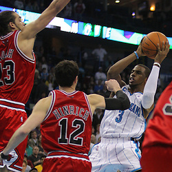 Jan 29, 2010; New Orleans, LA, USA; New Orleans Hornets guard Chris Paul (3) passes the ball past Chicago Bulls guard Kirk Hinrich (12) and center Joakim Noah (13) during the fourth quarter at the New Orleans Arena. The Bulls defeated the Hornets 108-106 in overtime. Mandatory Credit: Derick E. Hingle-US PRESSWIRE