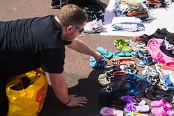 London, June 14th 2017. As fire rages through a residential tower block, Grenfell Tower, in Kensington, West London, local residents show their generosity as well-wishers pour into the Maxilla Social Club with clothing, food, water and blankets for the residents of the block who will have lost everything. PICTURED: A man donates a bag full of children's shoes.