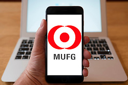 Using iPhone smartphone to display logo of MUFG , Mitsubishi UFJ Financial Group, a Japanese bank holding / financial services company