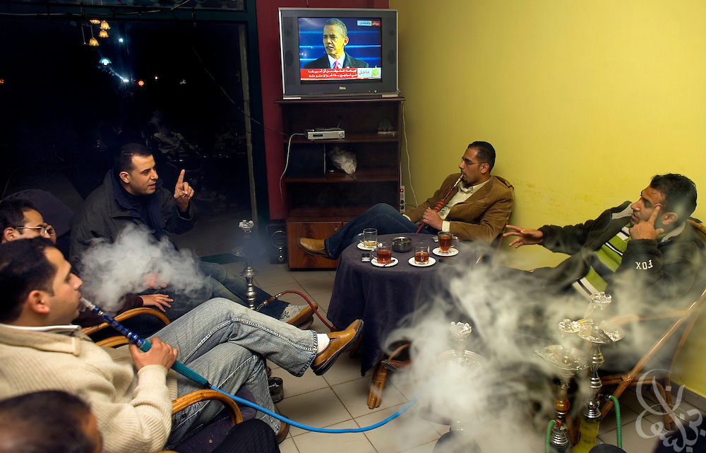 Palestinian men smoke traditional Middle Eastern water pipes as they watch and discuss the Obama inauguration live on Al Jazeera at a cafe in Gaza City January 20, 2009. Palestinians watched the inauguration with interest, and seem generally hopeful of the changes the Obama presidency will bring, but are also skeptical that he will be able to solve the ongoing problems between Palestine and Israel.